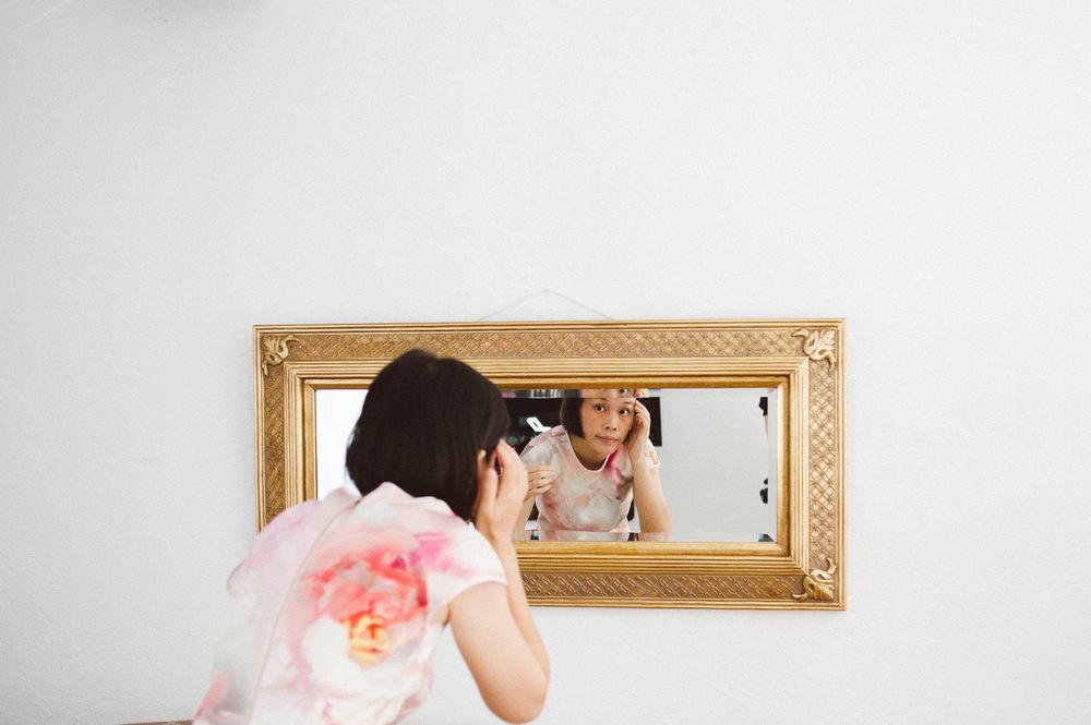 girl looks in mirror