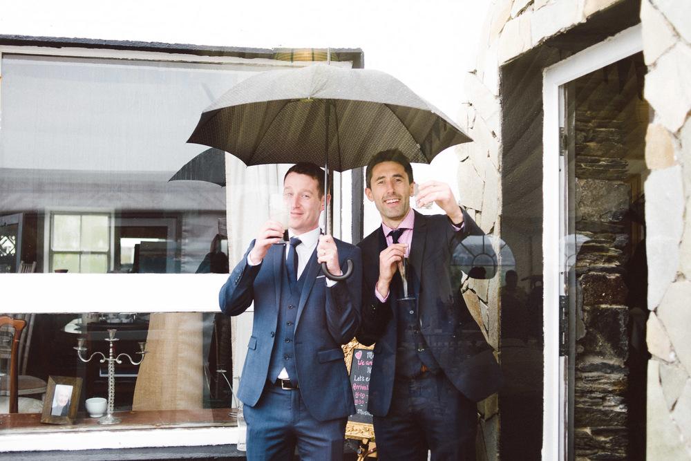 wedding guests stand under umbrella