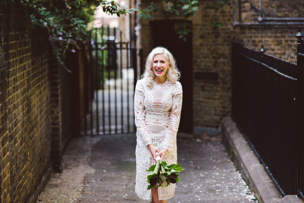 bride stands in alley way