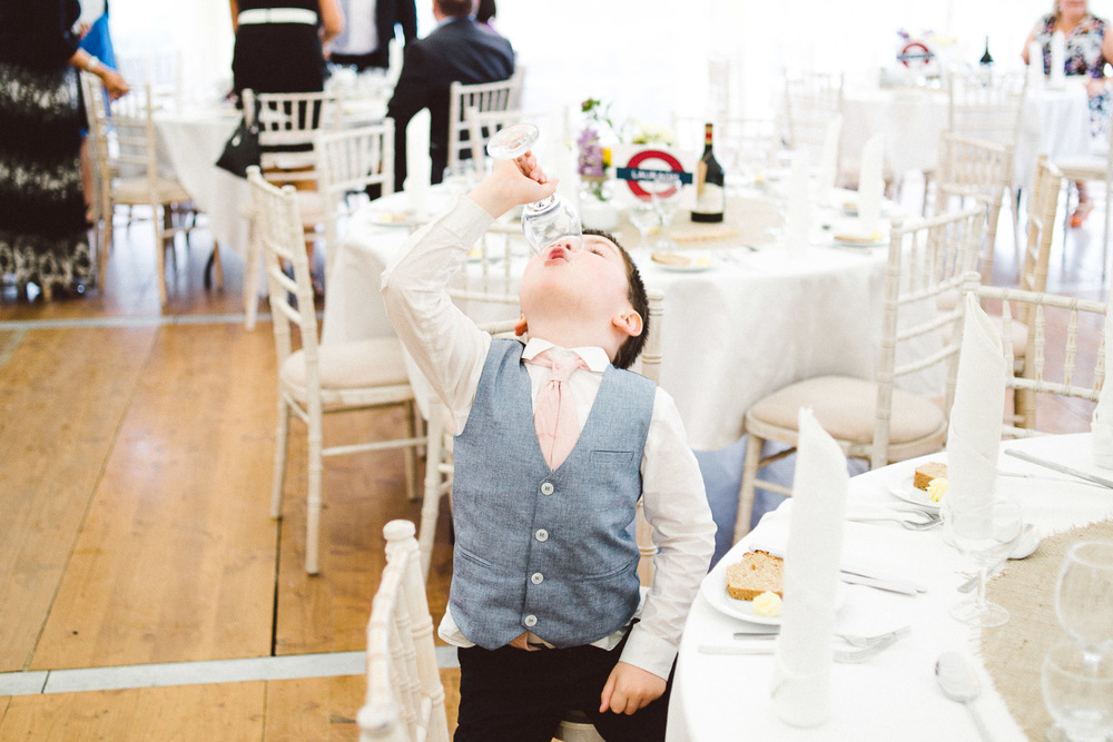 little boy takes drink from wine glass