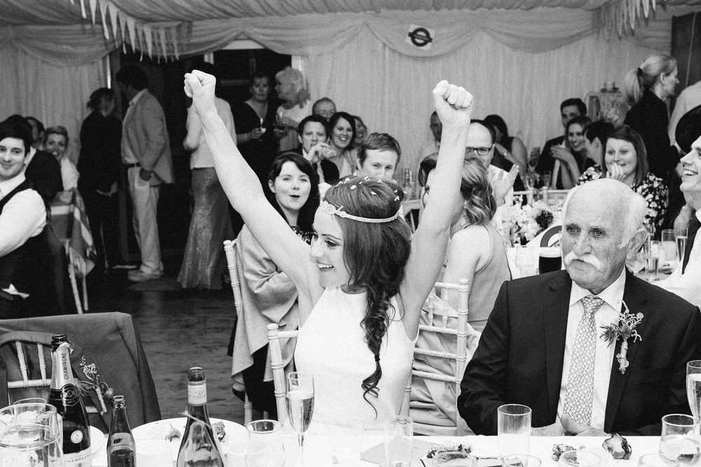 bride puts arms in the air smiling
