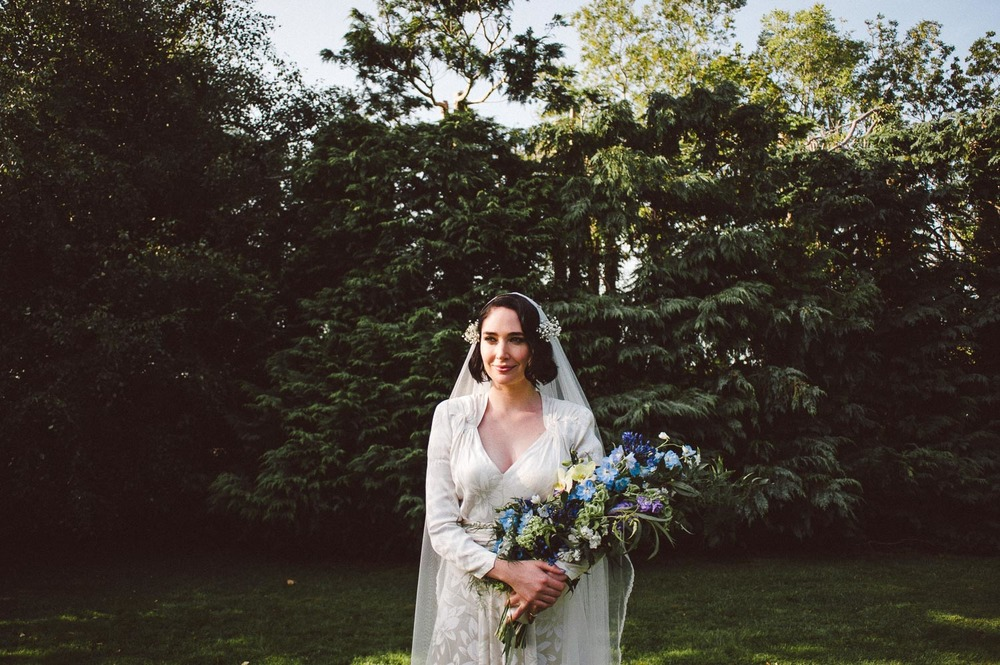 bride holds flowers outside in trees