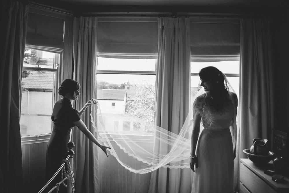 bridesmaid lifts out brides veil