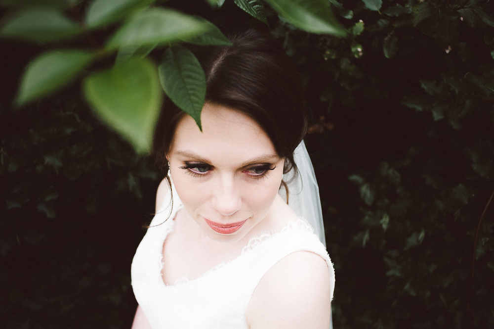 close up of brides face through leaves
