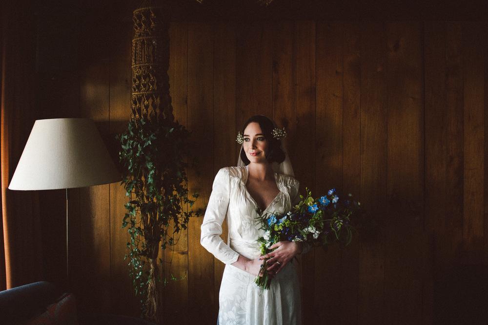 bride standing holding her flower beside window