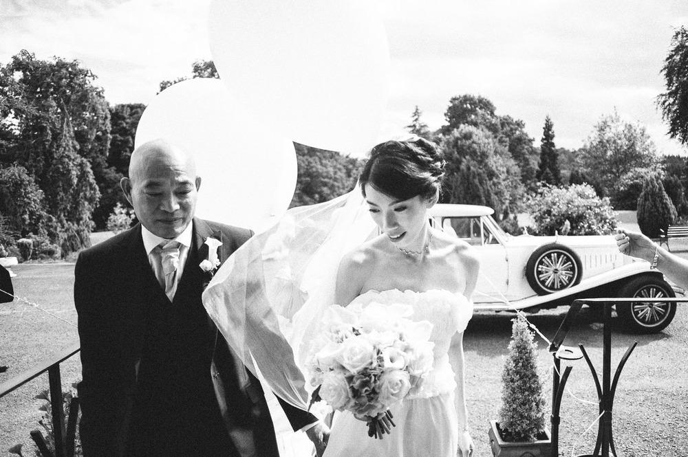bride and father walk into venue