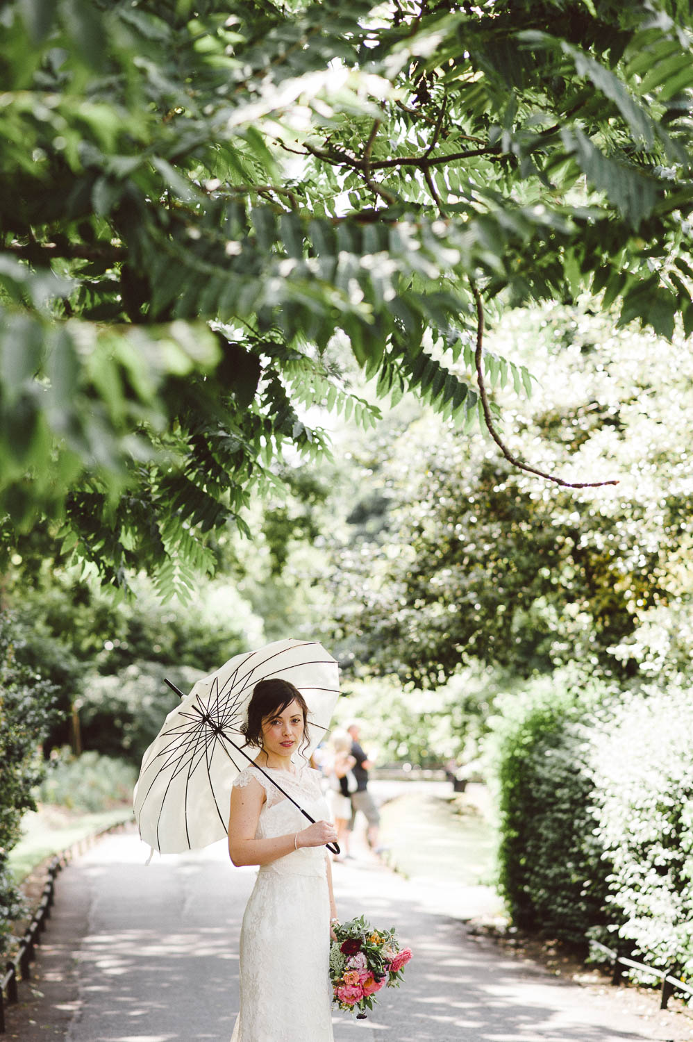 bride with parasol in greenery park