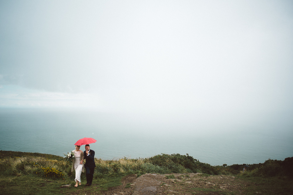 bride and groom take shelter under red umbrella