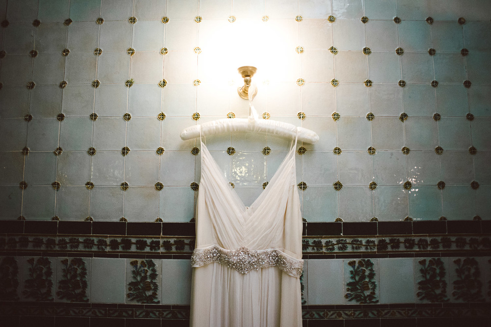 wedding dress hanging with a backdrop of beautiful green tiles.