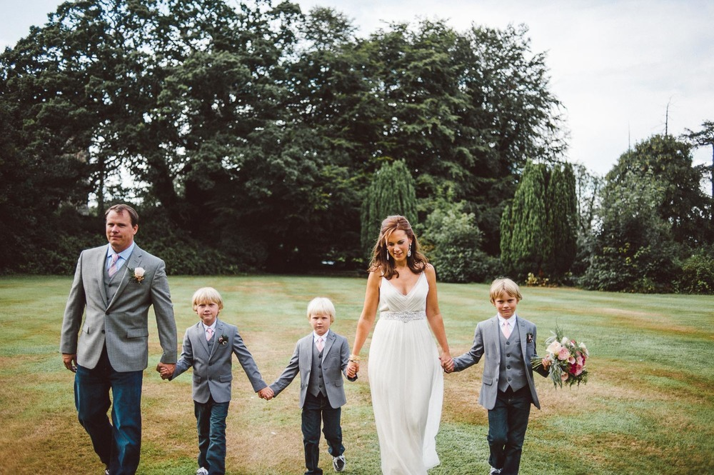 bride and groom walk wth their 3 kids