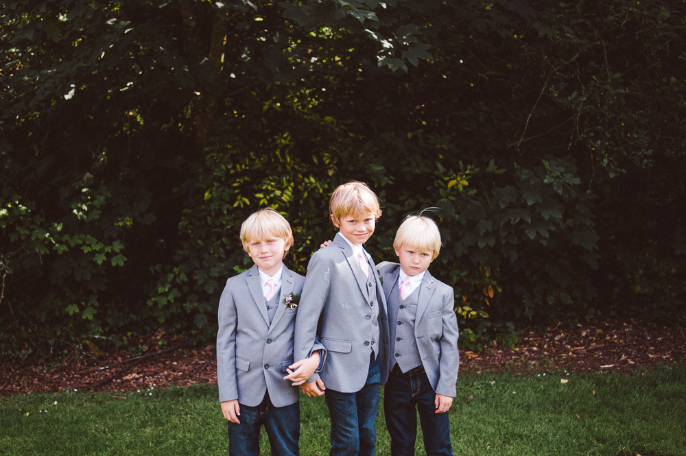 3 kids in grey suits and pink ties at wedding