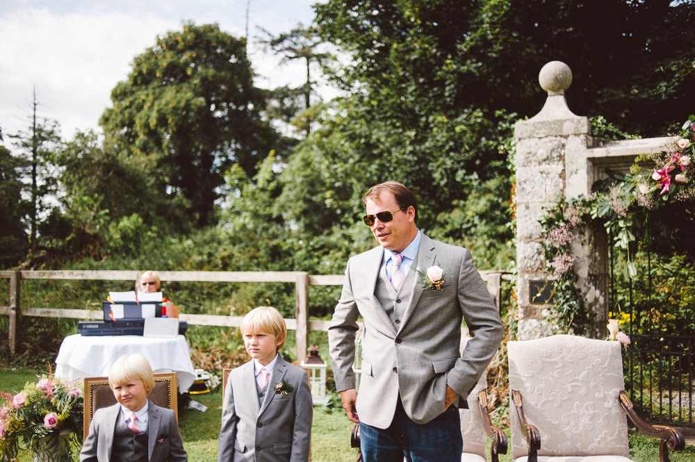 groom waits on bride with son and wears glasses