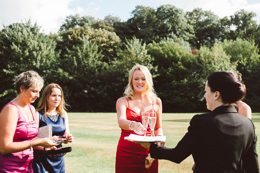 wedding guest in red dress takes champagne