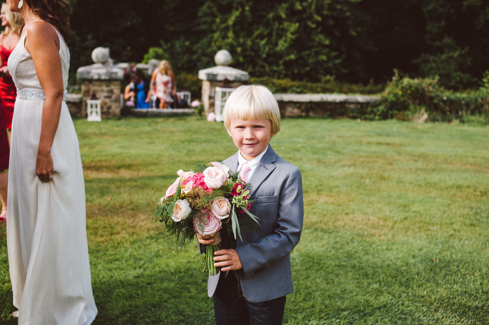 little page boy holds brides flowers