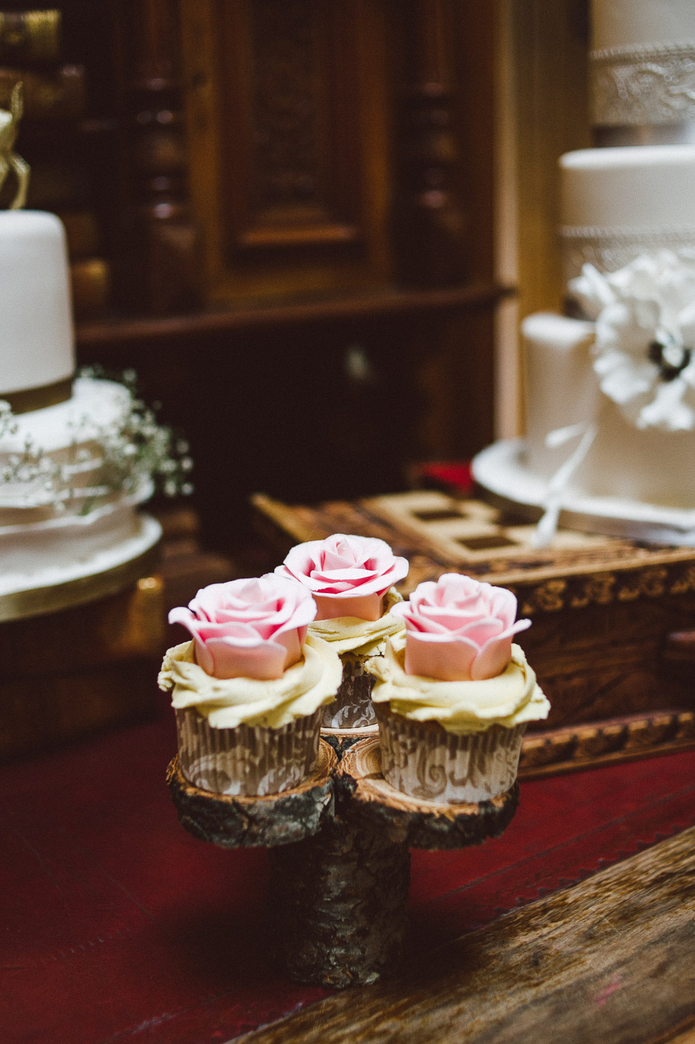 tiny cup cakes sitting on a tree log