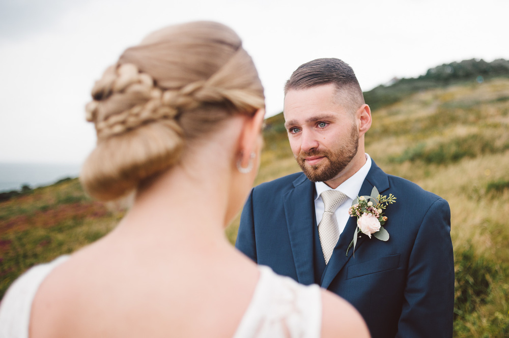 groom stands with tears in his eyes as bride reads vows