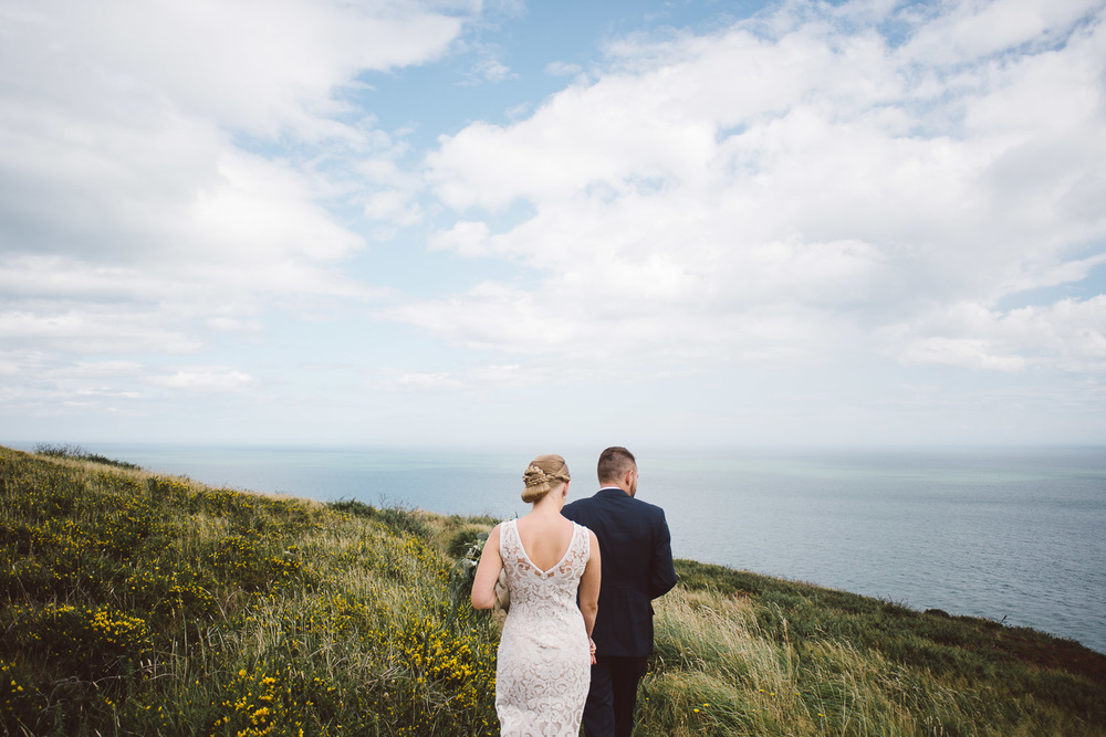 groom leads bride across howth head