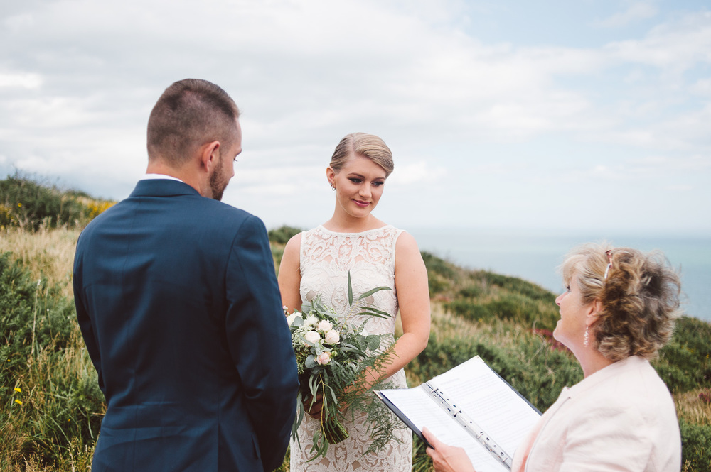 bride looks down at celebrant during elopement