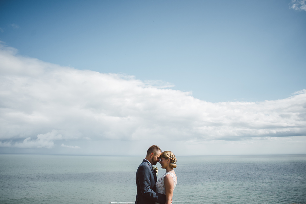 bride and groom head to hear with the view of the ocean