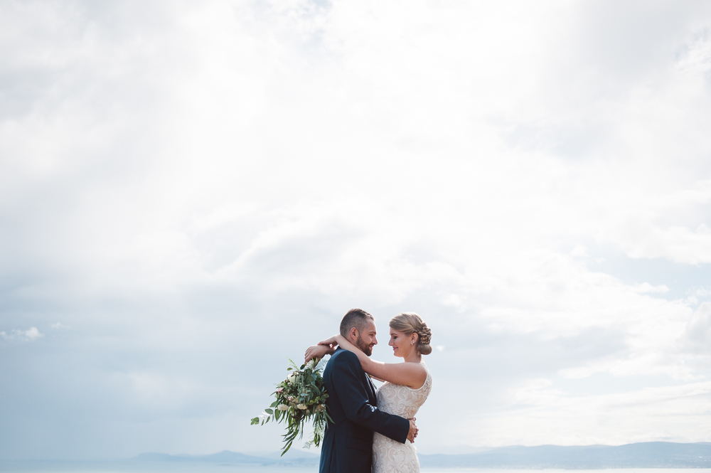 bride and groom hugging in front of a blue sky