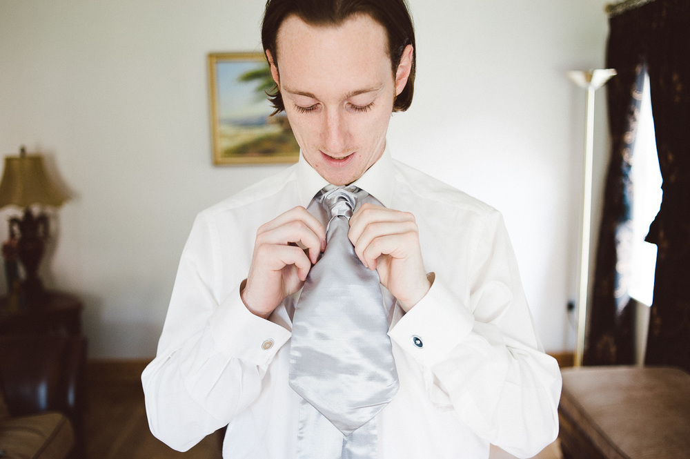 groom fixes his tie