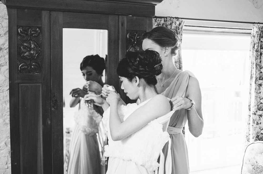 Bridesmaid helps bride into dress