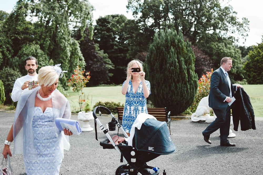 wedding guests with pram take photo