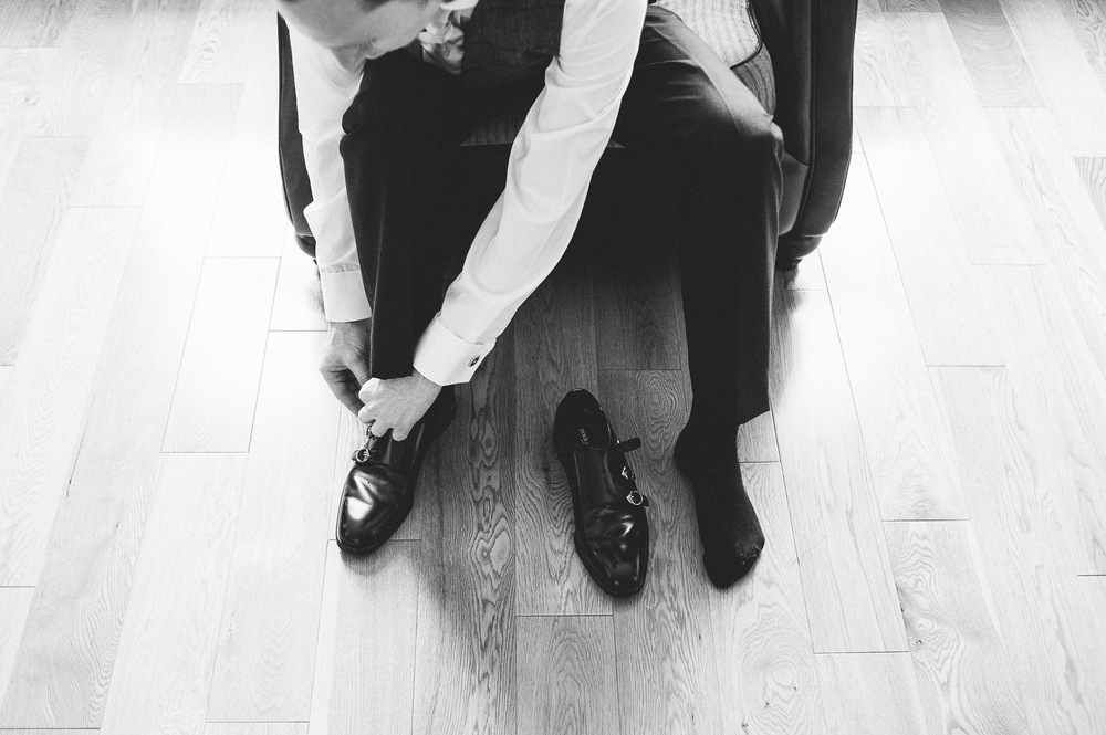 groom putting on his wedding shoes