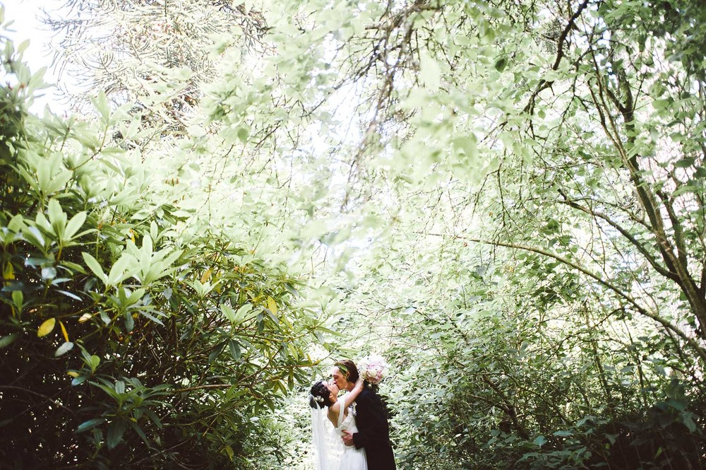 bride and groom kiss surrounded by trees