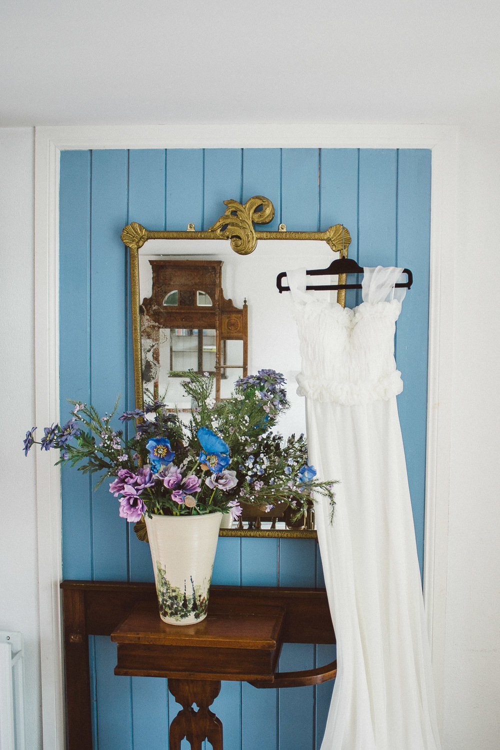 Brides dress hanging beside mirror