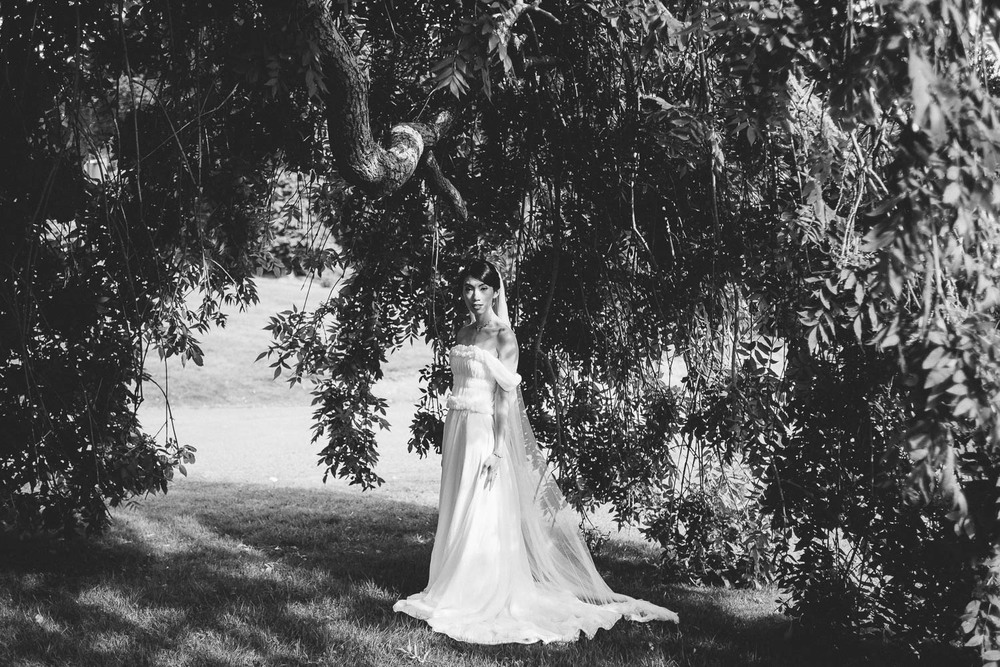 bride stands under a tree alone. Parkanour Manor House Wedding.
