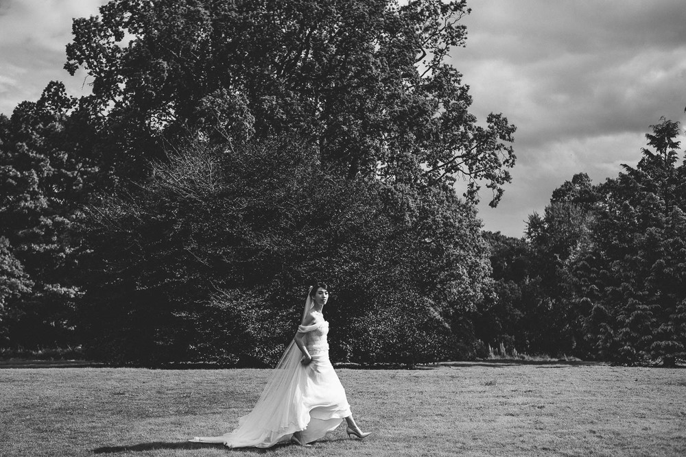 bride walks in front of huge trees. Parkanour Manor House Wedding.