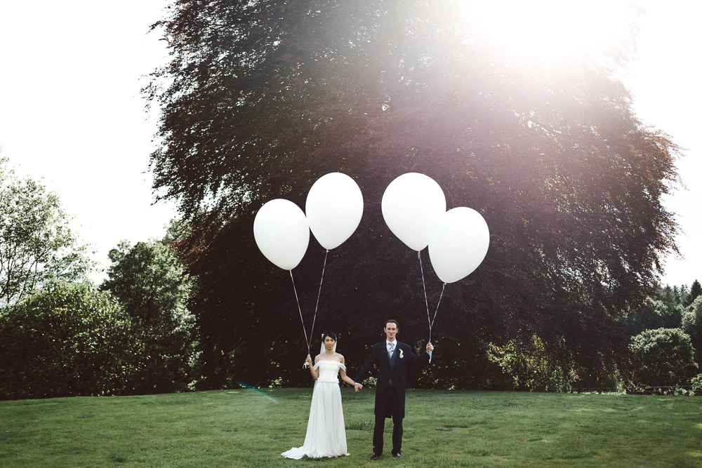 Parkanour Manor House Wedding. bride and groom stand holding balloons.