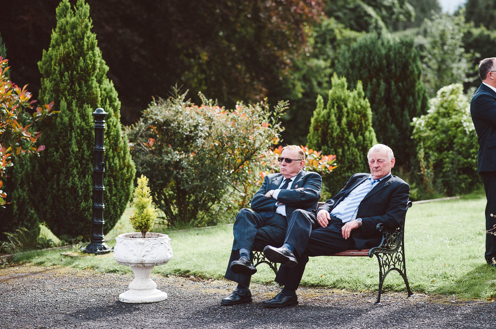 two men in suits sit on summer seat