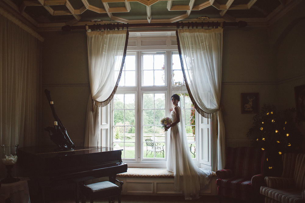 Parkanour Manor House Wedding. Bride stands at window