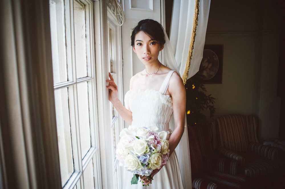 bride looking into camera beside window. Parkanour Manor House Wedding.