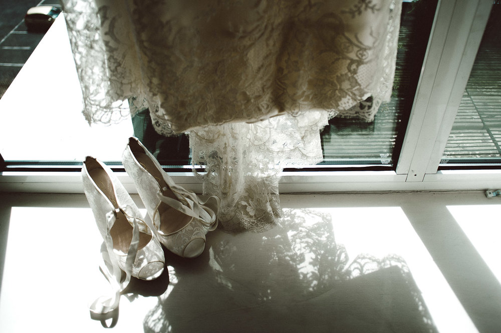 wedding shoes hanging by dress