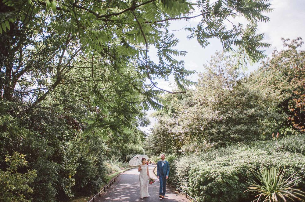 bride and groom walking among trees in st stephens green