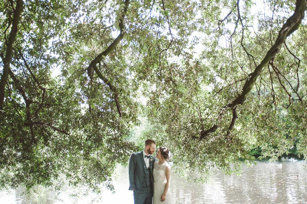 bride and groom under tree in front of lake