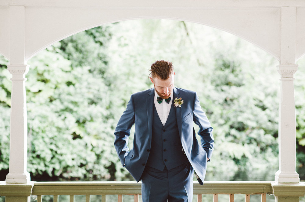 groom fixes his blue wedding jacket