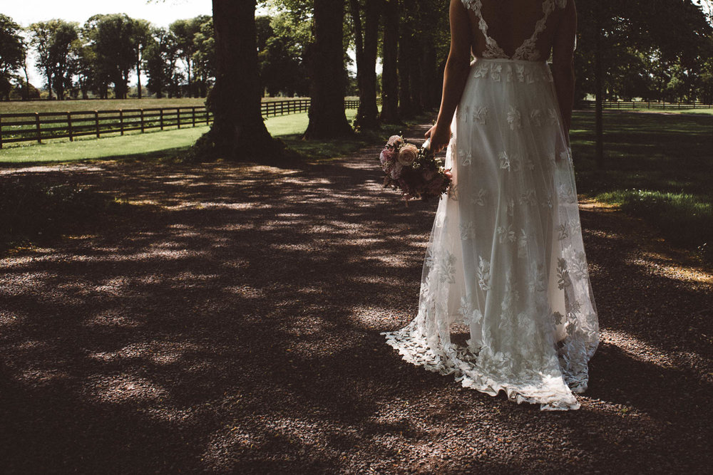 brides lace dress in dappled light