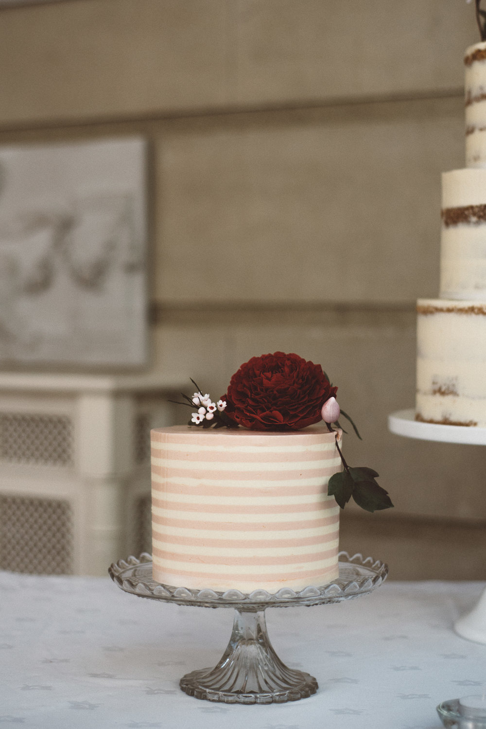 small pink and cream stripped wedding cake with red flower