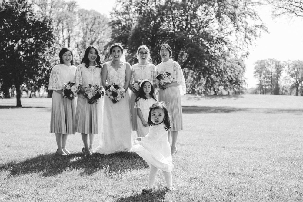 little girl pulling dress up infant of bridal party