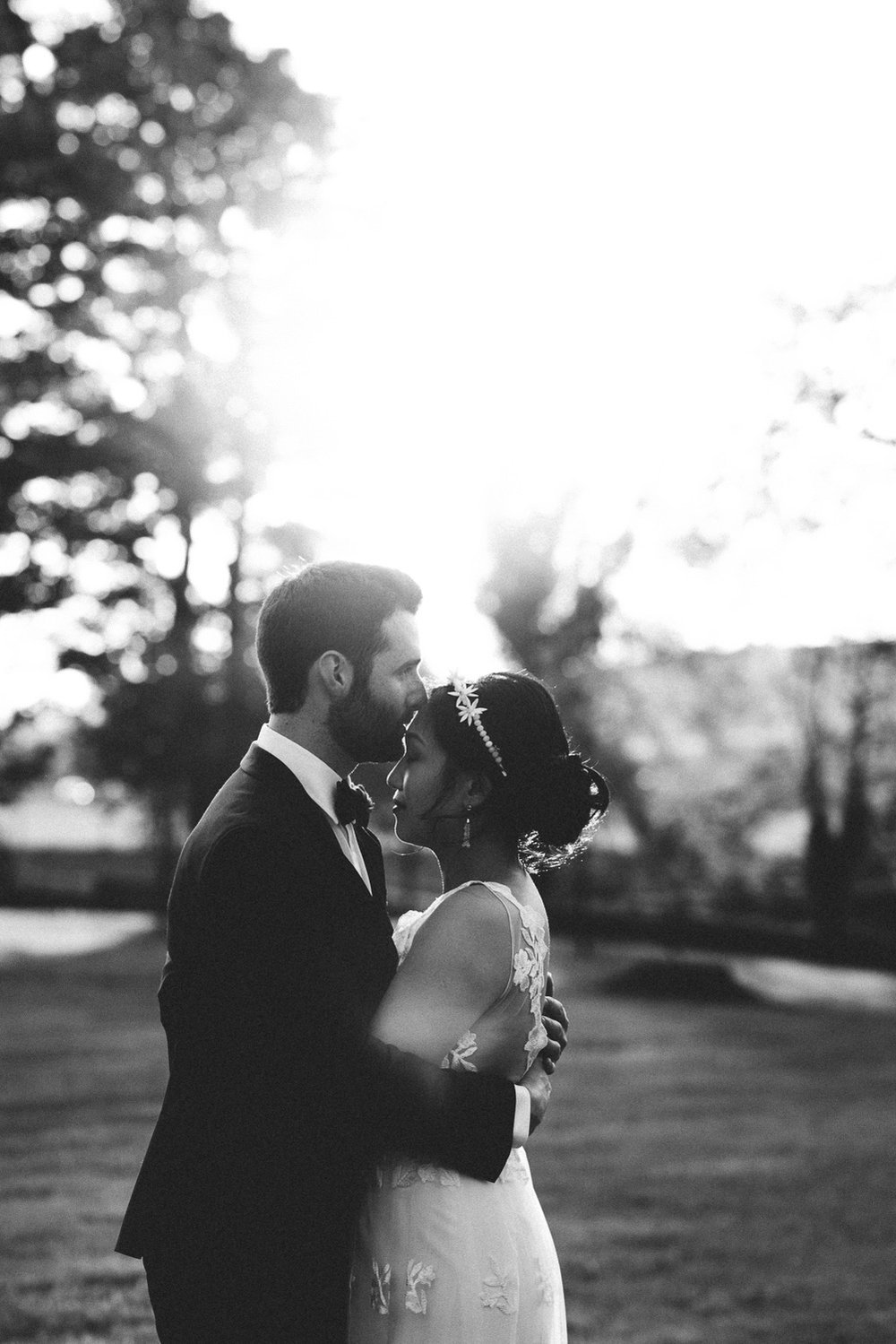groom kissing brides forehead at sunset