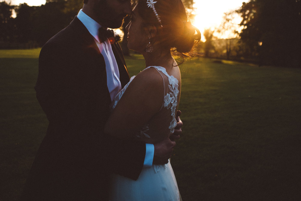 close up of grooms hands hugging brides back at sunset