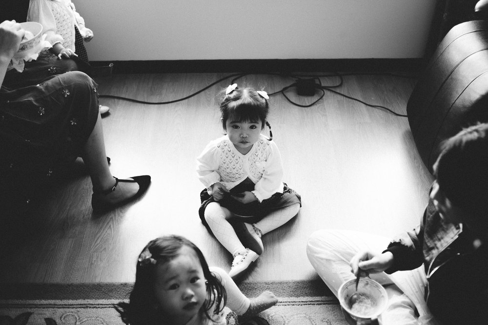 little girl sitting on floor looking into camera