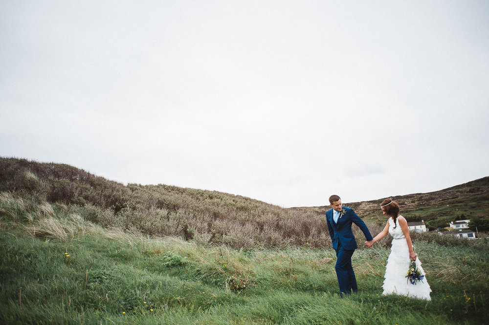 groom leads bride up grassy hill