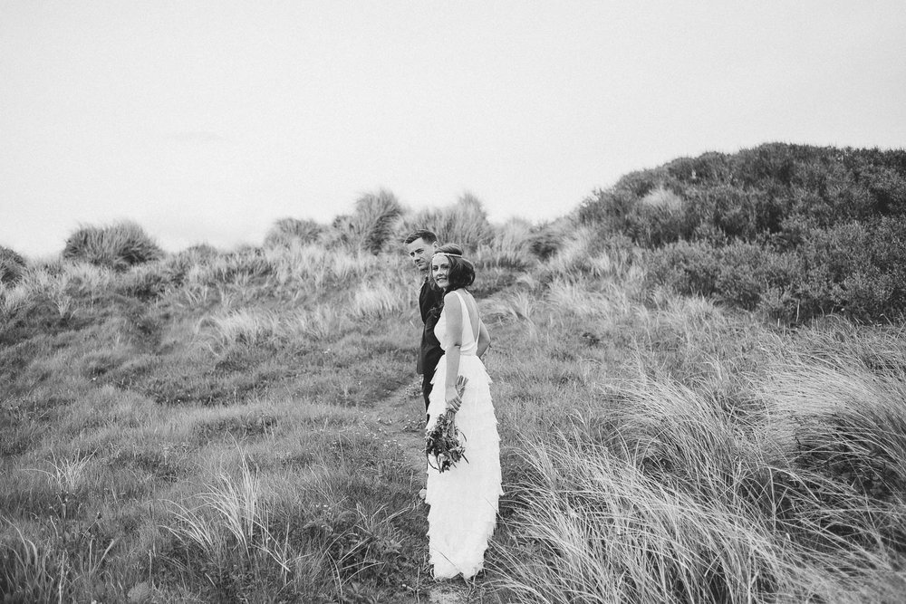 bride and groom stand in long grass