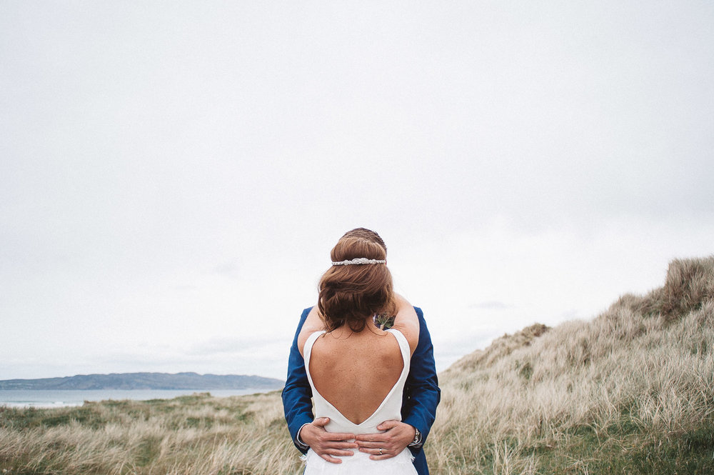 brides dress from behind and grooms hands around her waist