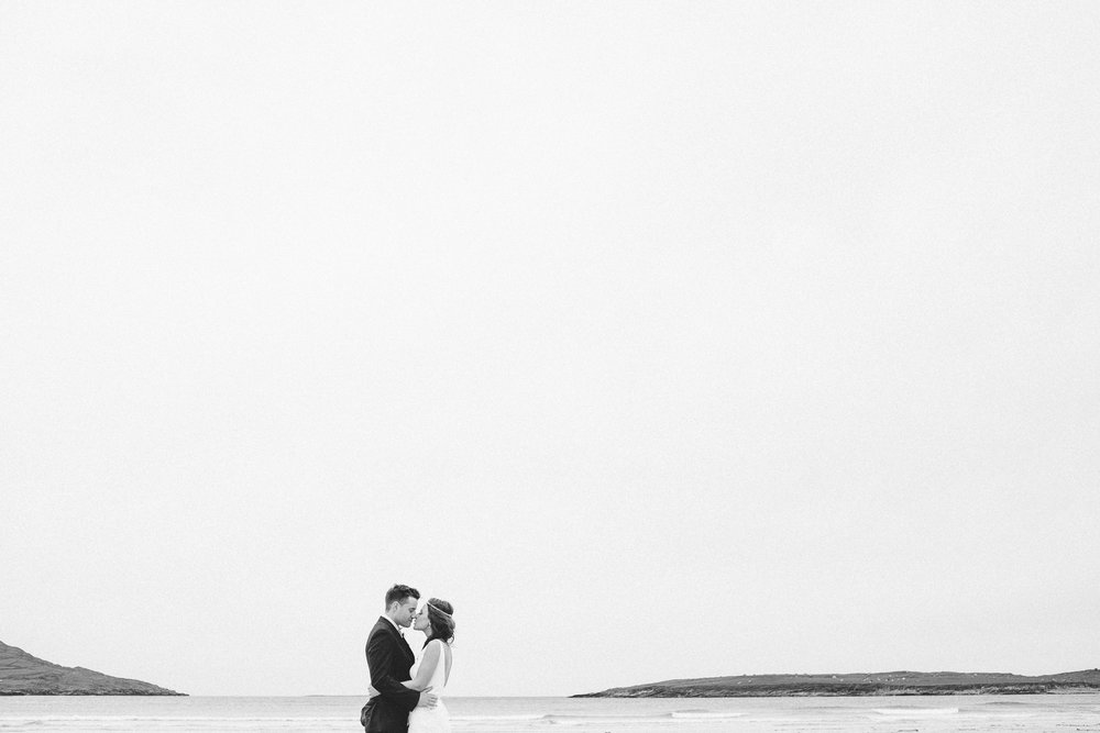 bride and groom kiss on a beach in donegal